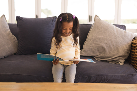 Front view of an African American girl reading a story book in living room at home