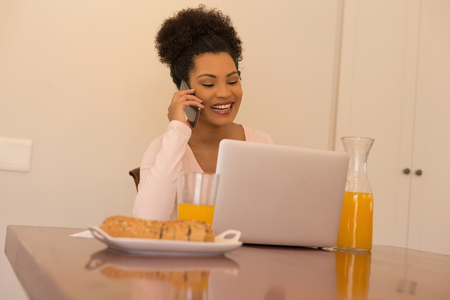 Front view of African American beautiful woman talking on mobile phone while using laptop at home Stock Photo