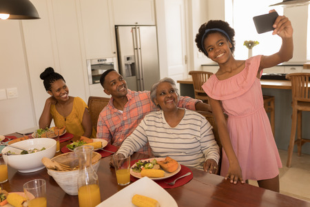 Front view of  African American happy girl taking a selfie of her family at the dinning table with her mobile phone at home