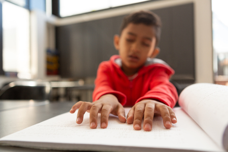 Front view of blind mixed-race schoolboy hands reading a braille book at desk in a classroom at elementary school