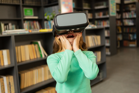 Front view of surprised Caucasian schoolgirl using virtual reality headset in library at elementary school