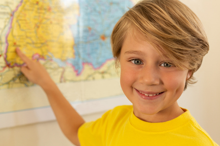 Front view of happy Caucasian boy looking at camera and pointing with his finger on a map in classroom at elementary school Stock Photo