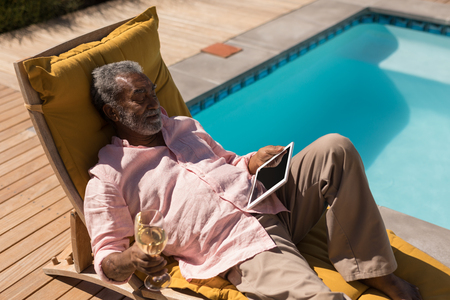 High angle view of an active African American senior man having champagne while using digital tablet on the lounger chair next to the swimming pool in the backyard of home
