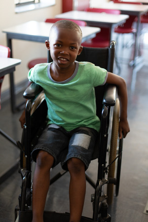 Front view of a African American disabled schoolboy looking at camera while sitting in a wheelchair in a classroom at elementary school