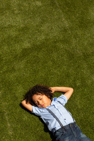 High angle view of a mixed-race schoolgirl relaxing in the school playground on a sunny day Imagens