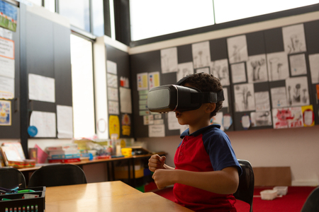 Side view of focused cute mixed-race schoolboy using virtual reality headset at desk in a classroom at elementary school