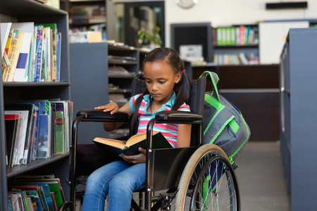 Front view of a disabled mixed-race schoolgirl reading a book in the library at school Stok Fotoğraf