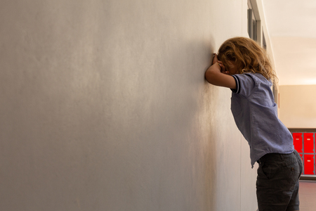 Side view of mixed -race sad schoolgirl leaning against wall in school corridor