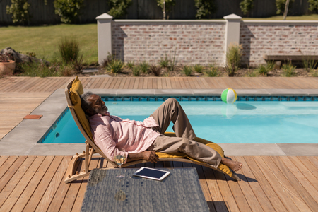 Side view of a senior  African American man sleeping on a sun lounger next to the swimming pool in the backyard of home