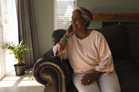 Front view of a thoughtful senior African American woman relaxing on a sofa in living room at home