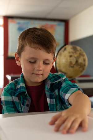 Front view of Caucasian blind boy reading a braille book at desk in classroom at elementary school Фото со стока