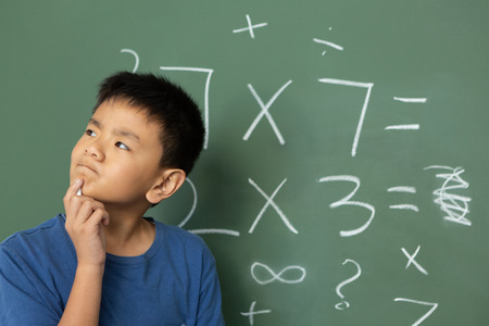 Front view of thoughtful Asian schoolboy doing math on green chalkboard in a classroom at elementary school