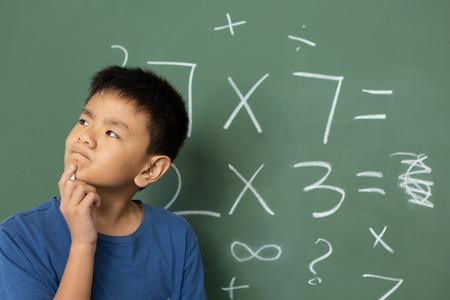 Vue de face d'un écolier asiatique réfléchi faisant des mathématiques sur un tableau vert dans une salle de classe à l'école primaire