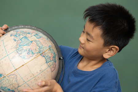 Front view of schoolboy looking at a globe while standing against green chalkboard in a classroom at elementary school