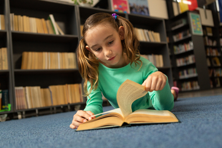 Front view of Caucasian schoolgirl lying on floor and turning a page in a book in library at elementary school