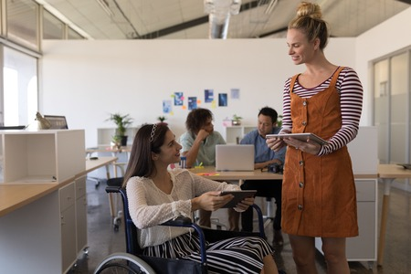 Front view of pretty disabled mixed-race female executive interacting with her casually dressed coworker in office