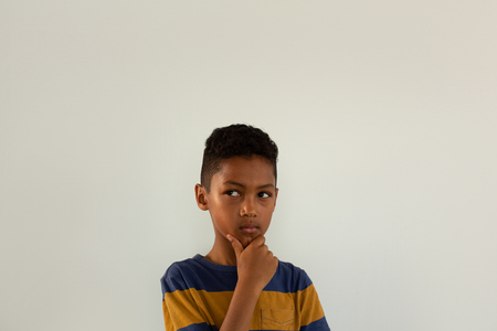 Front view of thoughtful mixed-race boy with hand on chin standing against white background Imagens - 121813105