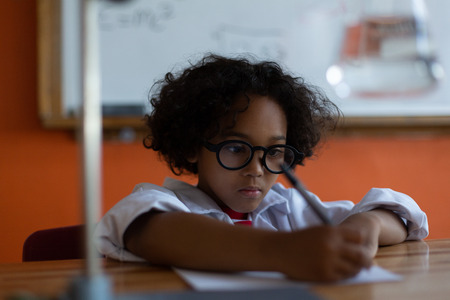 Front view of Mixed-race schoolboy writing on paper at desk in laboratory at school