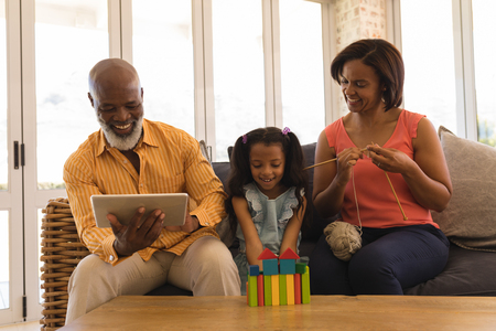 Front view of happy African American multi-generation family enjoying their free time in living room at home Stockfoto