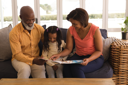 Front view of a happy African American multi-generation family reading a story book in living room at home