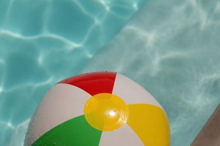 Inflatable ball floating in swimming pool on a sunny day Imagens
