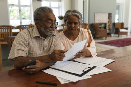 Front view of an active African American senior couple discussing over invoices in the living room at home