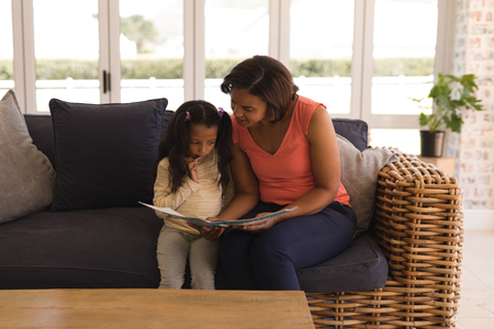 Front view of a happy African American grandmother and granddaughter reading a story book in living room at home