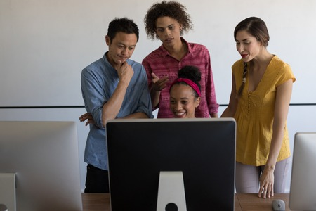 Front view of diverse casually dressed business colleagues discussing plans over computer in modern office Stockfoto