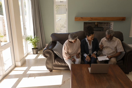 Front view of a senior African American man signing property contract with real estate agent and senior woman while sitting o the sofa in living room at home Stock Photo