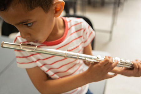 Close-up of focused mixed-race schoolboy playing flute in a classroom at elementary school