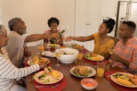 Vista frontal de una feliz familia afroamericana de varias generaciones comiendo juntos y el abuelo está vertiendo vino en la mesa del comedor en casa Foto de archivo