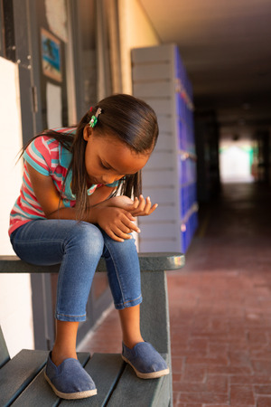 Front view of a sad mixed-race schoolgirl sitting alone on the bench in the corridor at school Stock Photo - 121813458
