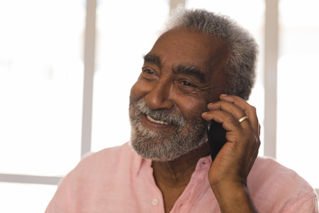 Front view of a smiling active  African American senior man talking on mobile phone at home