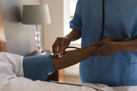 Mid section of African American female doctor measuring blood pressure of senior African American man and listing with stethoscope in bedroom at home