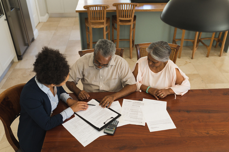 High angle view of a female African American real estate agent and a senior couple discussing over documents at the table of the living room at home Stock fotó - 121813395