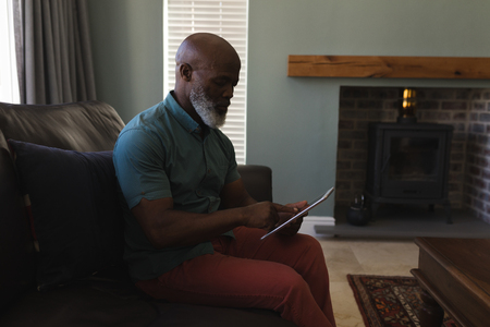 Side view of a senior man using digital tablet while sitting on the sofa in living room at home