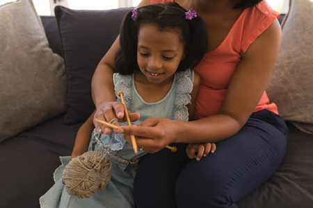 Close-up of an African American grandmother teaching her granddaughter how to knitt in living room at home