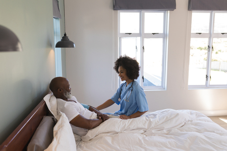 Side view of young African American female doctor consoling senior African American man in bedroom at home