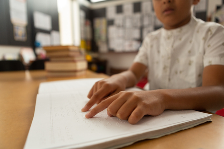 Mid section of blind focused mixed-race schoolboy reading a braille book in classroom at elementary school