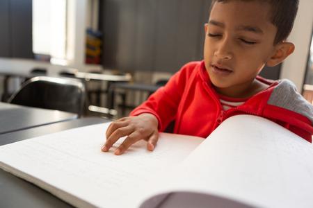 Vista frontal del colegial ciego de raza mixta leyendo un libro en braille en un escritorio en un aula en la escuela primaria