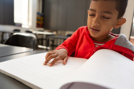 Front view of blind mixed-race schoolboy reading a braille book at desk in a classroom at elementary school