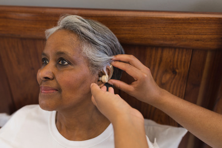 Close-up of African American female doctor fitting senior African American woman with hearing aid at home