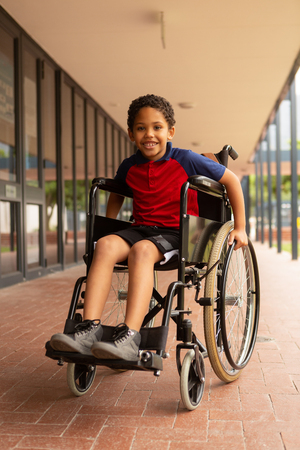 Front view of happy mixed-race disabled schoolboy looking at camera in corridor at elementary school