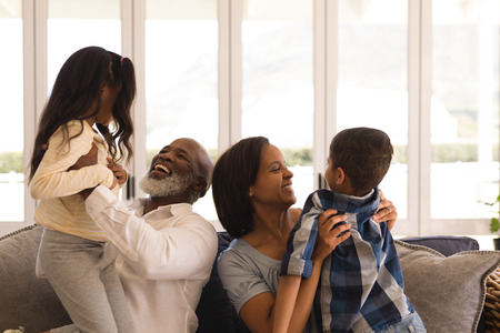 Front view of a happy multi-generation African American family having fun in living room at home Stock Photo