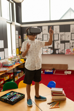 Front view of a cute mixed-race schoolboy using virtual reality headset on a desk in classroom at school