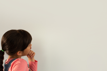Side view of thoughtful mixed-race girl with hand on chin standing against white background