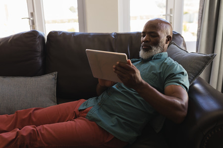 Side view of a senior man using digital tablet on the sofa in living room at home