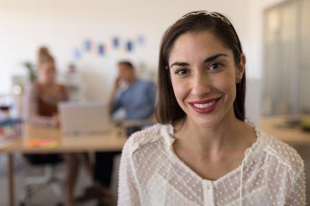 Retrato de hermosa mujer ejecutiva caucásica feliz sonriendo en la oficina moderna