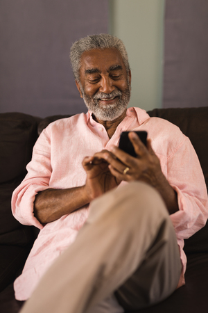 front view of an active African American senior man using mobile phone while sitting on a sofa in living room at home