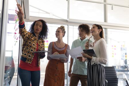 Vista frontale ad angolo basso di colleghi di lavoro multietnici che discutono di piani su note adesive in un ufficio moderno